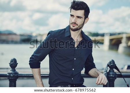 Portrait of handsome young man standing at riverside, looking away.