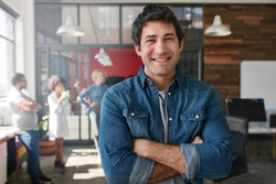 Portrait of handsome young man standing with his arms crossed in creative office. Confident young male creative professional looking at camera and smiling.