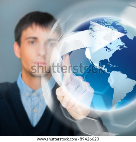 Portrait of handsome young man touching virtual globe. Global networking concept