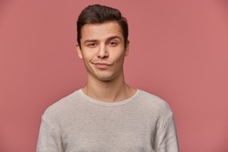 Portrait of handsome young man with raised eyebrow in disapproval, wears in blank t-shirt, looks at the camera with a grin and doubts, stands over pink background.