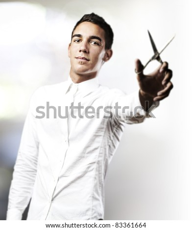portrait of handsome young man with scissors in a house