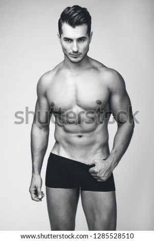 Portrait of handsome young man with stylish haircut in black underwear posing over gray background. Perfect hair & skin. Close up. Studio shot
