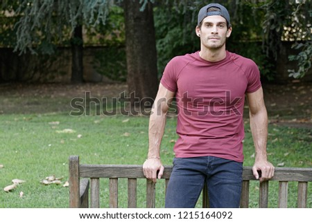 Portrait of handsome young muscled guy with red t-shirt in a park #1215164092