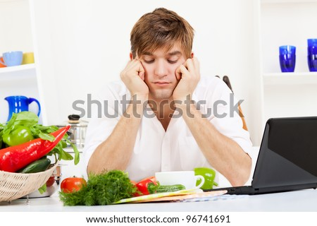 portrait of handsome young sad man cooking in the kitchen, problem prepare vegetable salad fail, upset bored man sitting at table with vegetables tired