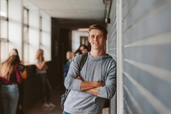 Portrait of handsome young university student standing and leaning to a wall in college corridor with other students at the back. Caucasian male student in high school campus.