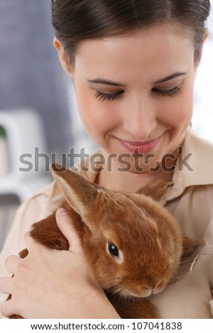 Portrait of happily smiling woman holding cute pet rabbit.