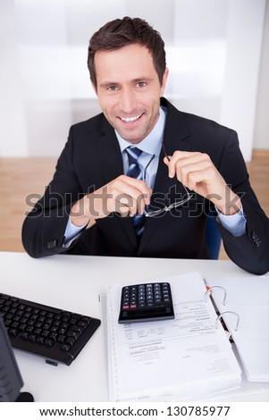 Portrait Of Happy Accountant At Workplace In The Office
