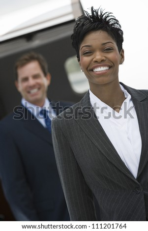 Portrait of happy African American businesswoman with colleague in the background at airfield