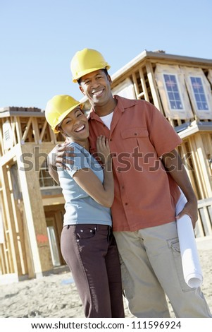 Portrait of happy African American couple at construction site
