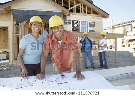 Portrait of happy African American couple at construction site with builders standing background