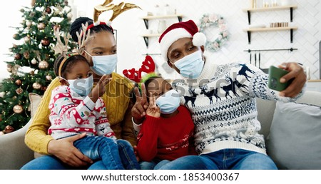 Portrait of happy African American family in masks taking pictures on smartphone in cozy christmassy decorated home. Dad in santa hat taking selfie photo on cellphone with kids and wife