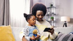 Portrait of happy African American family pretty mother and small adorable daughter sitting on sofa browsing online on smartphone watching cartoons. Mom and child searching internet on cellphone