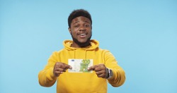 Portrait of happy African American man holding in hands euro banknotes isolated over blue background. Euro Money.