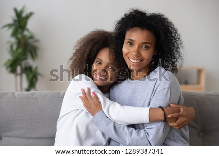 Portrait of happy African American mom and teen daughter spend time at home together, hugging on couch, smiling teenage girl embrace young black mother or nanny, show love and affection stock photo