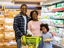 Portrait of happy African American parents with their daughter shopping for groceries at supermarket. Young black family buying products, purchasing food at hypermarket or mall