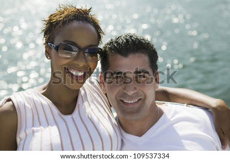 Portrait of happy African American woman standing with around man on the yacht