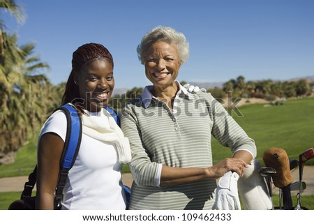 Portrait of happy African American woman with granddaughter at golf course
