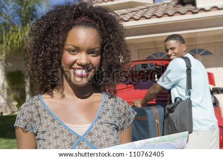 Portrait of happy African American woman with man keeping luggage in car - stock photo