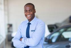portrait of happy african car salesman in showroom