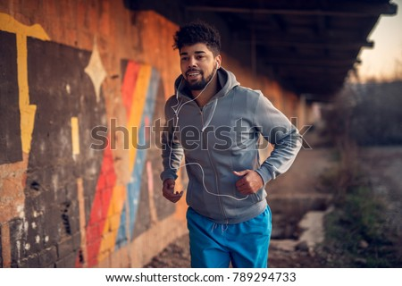 Portrait of happy afro-american attractive active runner man jogging outside on abandon place with earphones. #789294733