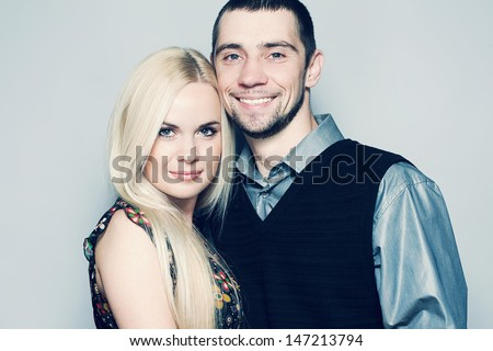 Portrait of happy and loving married couple posing together over light blue background. Casual urban style. Close up. Copy-space. Studio shot