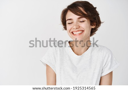 Portrait of happy and positive woman close eyes, smiling carefree, standing in t-shirt on white background.