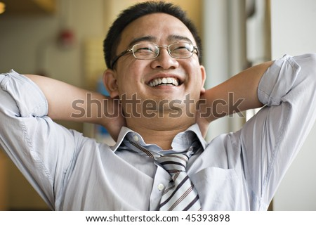 portrait of happy asian business executive; hands behind head