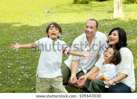 Portrait of happy asian caucasian family in the park