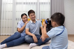 Portrait of happy Asian couple take a pictures by son in living room at home, Little boy photographer and Family relax lifestyle concept