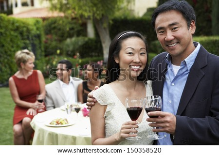 Portrait of happy Asian couple toasting wine with friends in background