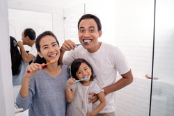 portrait of happy asian family brush their teeth together in bathroom sink. parent brush teeth and take care of kid