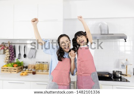 Portrait of Happy Asian family in the kitchen. Mother and Little girl in apron set good mood. Hands up Smile and glad