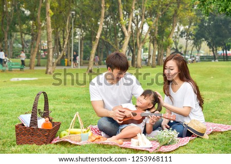 Portrait of happy Asian family, parents and daughter enjoying picnic meal in garden.Asian, Asian family, picnic, love, relationship, outdoors meal, park, family activities or happy garden concept