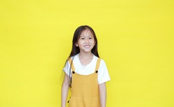 Portrait of happy asian little girl in dungarees with smiling isolated on yellow background