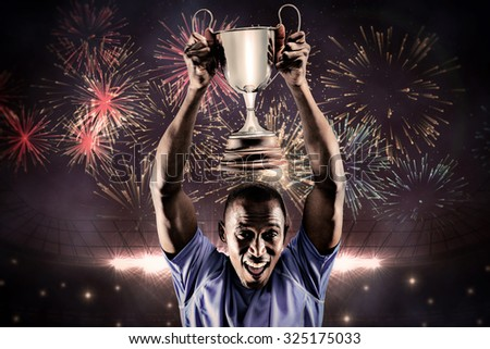 Portrait of happy athlete cheering while holding trophy against fireworks exploding over football stadium