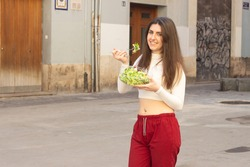 Portrait of happy attractive caucasian young woman model eating and showing ealthy fresh salad in a bowl. Dieting concept. Healthy lifestyle with green food, in the city, white top and red pants. Plac