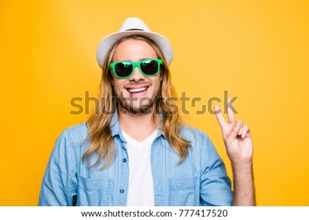 Portrait of happy, attractive guy in summer glasses with beaming smile showing v-sign in camera standing over yellow background #777417520