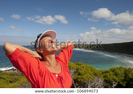 Portrait of happy attractive looking mature middle aged woman joyful laughing, isolated with sunshine on face, ocean, sly and coastline as background and copy space.