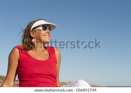 Portrait of happy attractive looking middle aged woman joyful laughing, isolated with sunshine on face, ocean and blue sky as background and copy space.