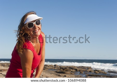 Portrait of happy attractive looking middle aged woman joyful laughing, isolated with sunshine on face, ocean, sky and coastline as background and copy space.