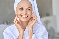 Portrait of happy attractive middle aged woman wearing bathrobe and white turban with bright complexion touching face looking away in bathroom. Advertising of skin care spa wellness concept.