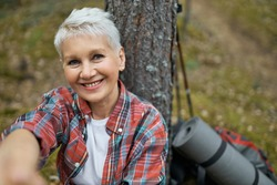 Portrait of happy attractive middle aged woman with blonde hair sitting under pine looking at camera with smile, reaching out hand as if taking selfie on smart phone, having break, hiking outdoors