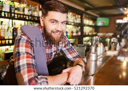 Portrait of happy attractive young bartender with shaker in pub #521292370