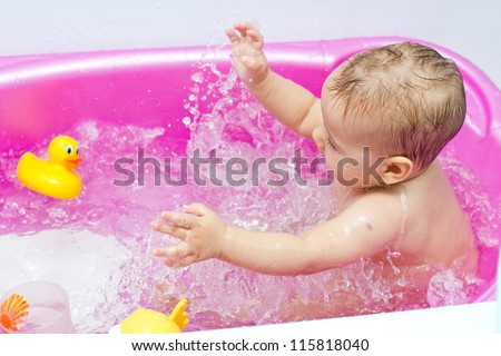 Portrait of happy baby while bath in bathtub with toys.