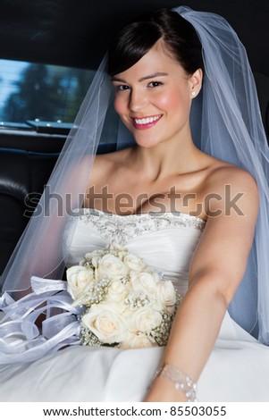 Portrait of happy beautiful bride in limousine