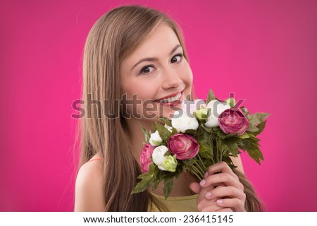 Portrait of happy beautiful brown haired girl holding  bunch of roses on rose background smiling looking at camera