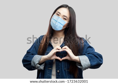 Portrait of happy beautiful brunette asian young woman with surgical medical mask in blue denim jacket standing with love heart gesture with smile. studio shot, indoor isolated on grey background
