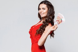 Portrait of happy beautiful brunette young woman holding rubles money.   Gray background. Sale, finance, banking, winning, economic, credit, business, shopping concept. RUB, Russian Ruble.