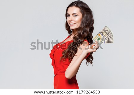 Portrait of happy beautiful brunette young woman in red dress holding dollars money. Gray background. Sale, finance, banking, winning, economic, credit, business, shopping concept. USD