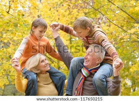 portrait of happy beautiful elderly couple and grandchildren rest fall